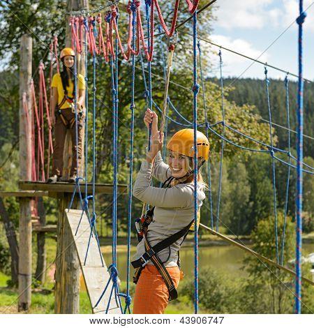 Smiling woman having fun in adventure park rope ladder