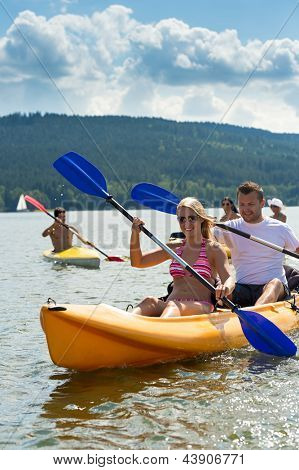 Young friends kayaking in summertime on lake holiday