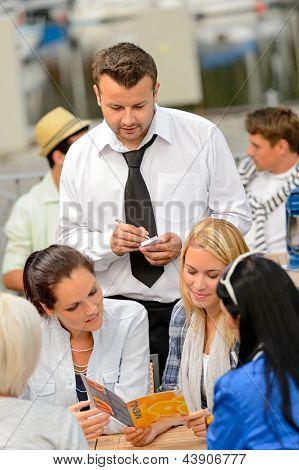 Women customers ordering from waiter at sidewalk restaurant