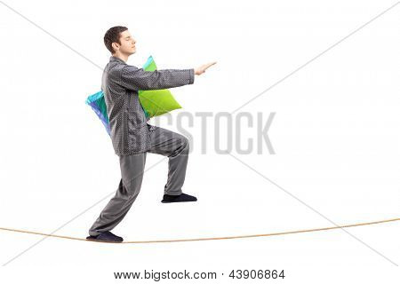 Full length portrait of a young man holding a pillow and sleepwalking on a rope isolated against white background