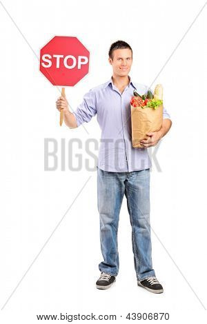 Stop and shop here  Full length portrait of a male holding a paper bag and a stop road sign isolated on white background