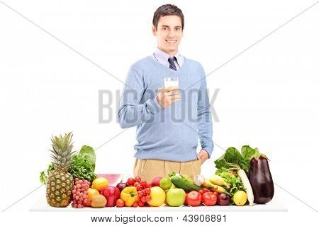 Young man holding a glass of milk and standing next to a pile of fruits and vegetables isolated on white background