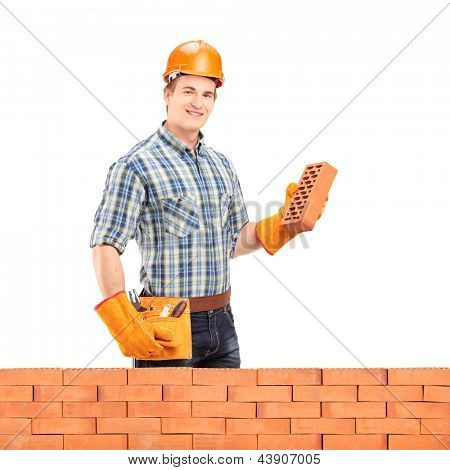 Male manual worker with helmet holding a brick behind a brick wall isolated on white background