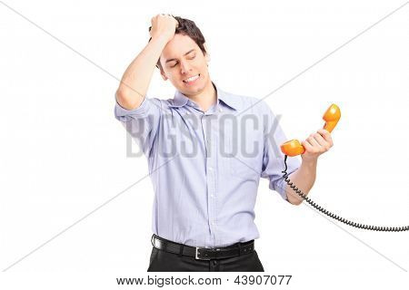 Young man in trouble holding a telephone tube, isolated on white background