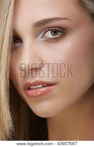 Close-up portrait of a pretty young woman with long blond hair and green eyes
