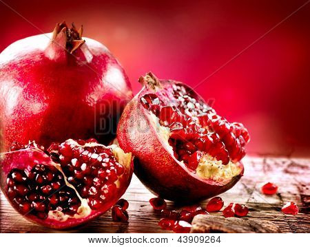 Pomegranate fruit. Pomegranates over Red Background. Organic Bio fruits