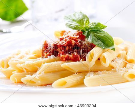 Pasta. Penne Pasta with Bolognese Sauce, Parmesan Cheese and Basil on served Table. Italian Cuisine. Mediterranean food