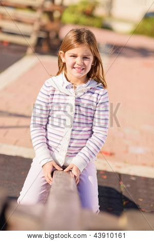 Little Blonde Girl Playing On Seesaw, Outdoors