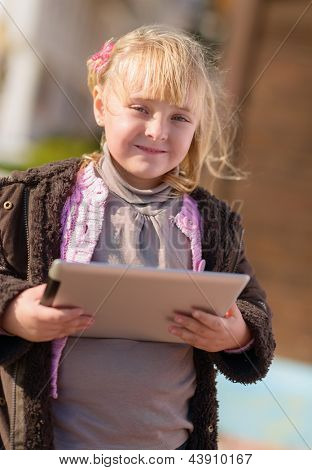 Happy Little Girl Holding Digital Tablet, Outdoors