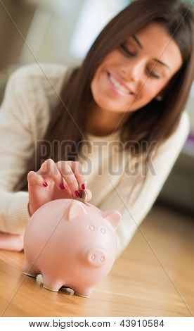 Young Woman Putting Coin In Piggy bank, Indoors