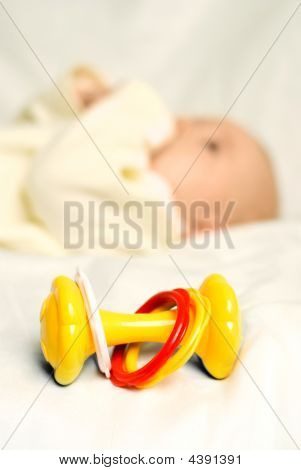 Little Baby Lies On The Bed With A Toy