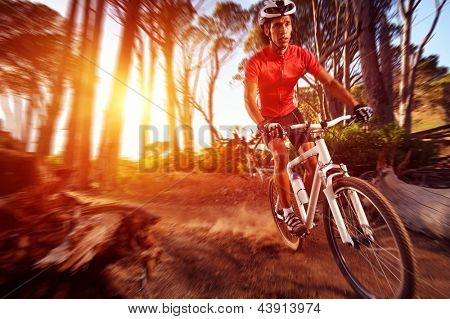Action motion blur mountain bike cyclist doing downhill extreme biking
