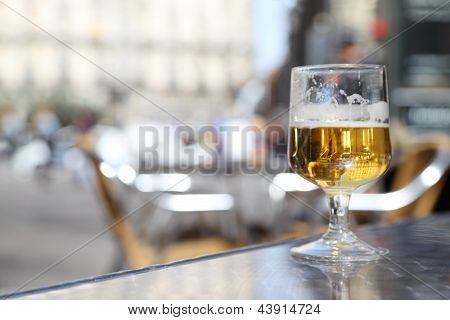 Half-finished glass of beer stands on gray windowsill. In beer reflects city streets.