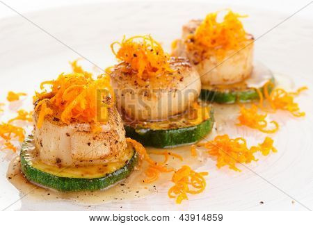 Seared scallops with citrus zest and sweet-sour sauce on plate