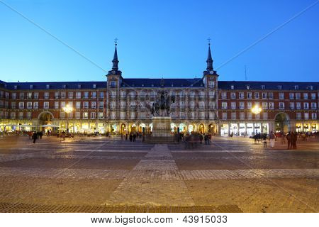 People walk near monument to Philip III Habsburg in Plaza Mayor at evening in Madrid, Spain.