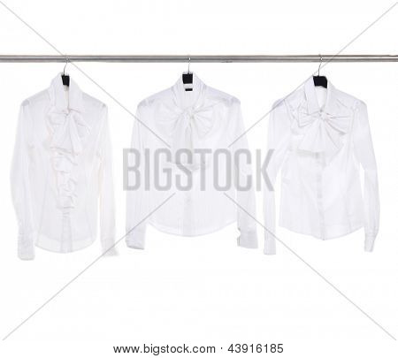 Three white female clothing on hanger in a row