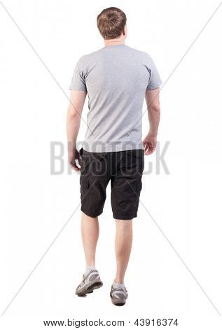 Back view walking handsome man Sports-dressed young man moves. going young guy. Rear view people collection.  backside view person. Isolated over white . broad-shouldered guy is looking forward right