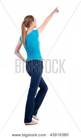 back view walking  woman pointing. beautiful blonde girl in motion.  backside view of person.  Rear view people collection. Isolated over white background. blonde teen while walking indicates that top