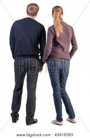 Back view young couple  hug. beautiful friendly girl and guy together. Rear view. Isolated over white. boy and girl  couples face with his hands in his pockets and looking at something interesting