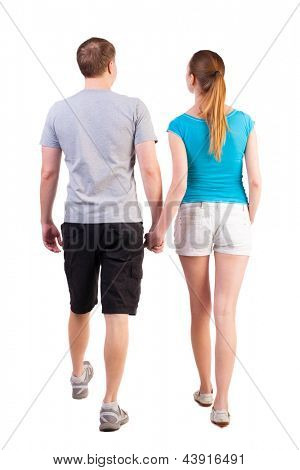 Back view of going young couple (man and woman). walking beautiful friendly girl and guy in shorts together. Rear view people collection.   backside view of person.