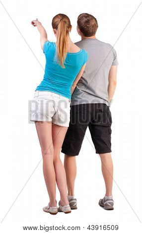 Back view of young couple pointing at wall (woman and man). Rear view people collection.   backside view of person.  Isolated over white background. by summer dressed teenagers refer to something far