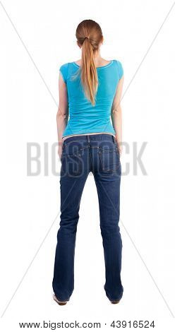 back view standing young beautiful  blonde woman in blue t-shirt and jeans. girl  watching. Rear view people collection. backside view person. she curiously looks up.  Isolated over white background