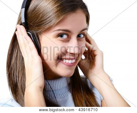 attractive teen girl listening to music on headphones and winking, portrait over white