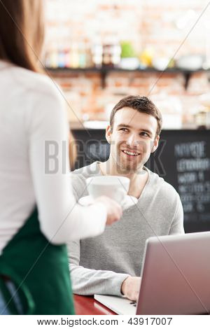 Waitress serving man at cafe