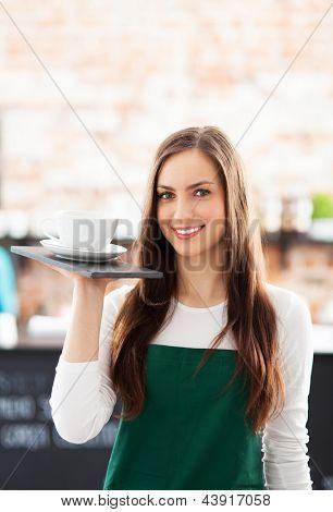 Garçonete, segurando a xícara de café no café