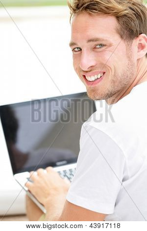Laptop man smiling happy using computer pc outside. Young white joyful caucasian model lifestyle image.