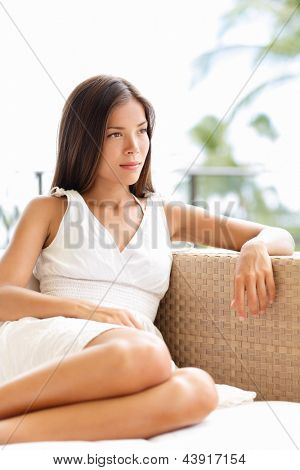 Confident serious sophisticated woman thinking and looking outdoors in luxury setting. Beautiful young multicultural Asian Caucasian female model in white dress relaxing outside.