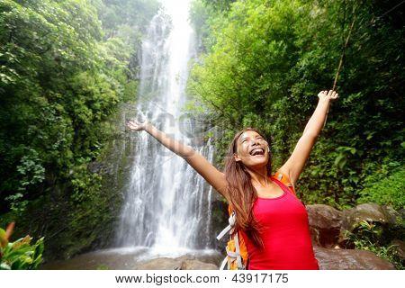 Hawaii vrouw toeristische opgewonden door waterfall tijdens reizen op de beroemde weg naar Hana op Maui, Hawaii.