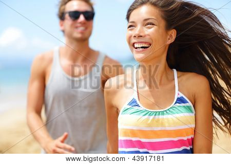 Young happy couple laughing having fun on beach. couple holding hands running playful and cheerful smiling happy on beach outside during summer vacation. Asian woman, Caucasian man.
