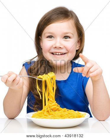 Little girl is eating spaghetti, isolated over white