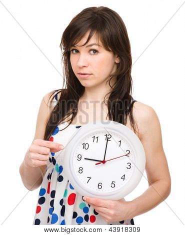 Young woman is holding big clock and pointing at it, isolated over white