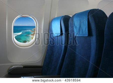 Airplane seat and window inside an aircraft with view on sea and coast in Uluwatu in Bali.