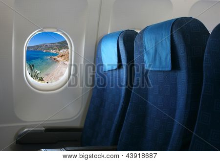 Airplane seat and window inside an aircraft with view on sea in Croatia.
