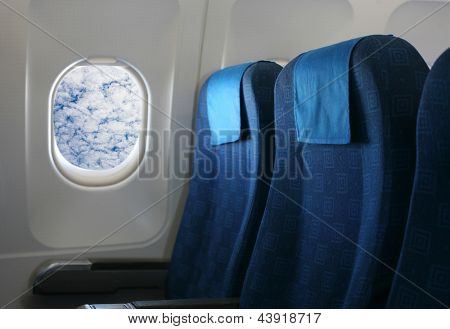 Airplane seat and window inside an aircraft with view of clouds