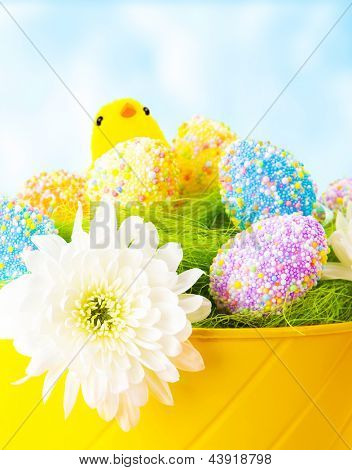 Closeup of colorful Easter eggs with chick toy in festive basket over blue sky background, traditional Christian celebration