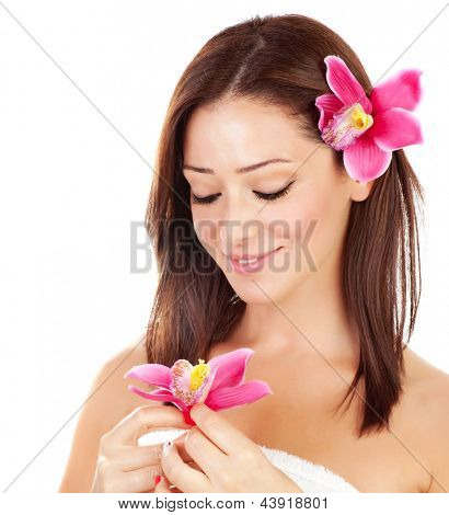 Attractive brunette female with pink orchid flowers in hair isolated on white background, cute girl with closed eyes enjoying day spa