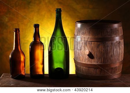 Wooden barrel with colors bottles on a dark yellow background.
