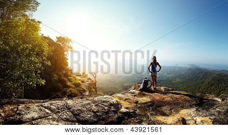 Hiker with backpack standing on top of a mountain and enjoying stunning valley view