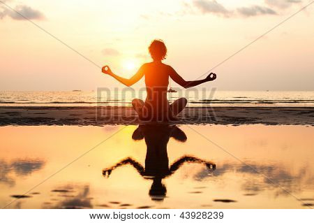 Yoga woman sitting in lotus pose on the beach during sunset in bright colors. (with reflection in water)