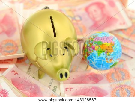piggy bank and one-hundred rmb bill with earth
