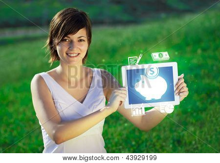 Young business woman looking at modern tablet with abstract light and various diagrams