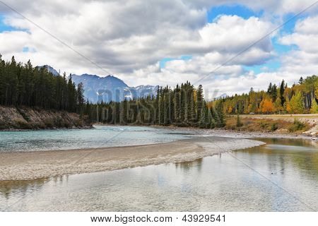 Shining silvery surface of the lake. Early autumn in the Rocky Mountains of Canada.
