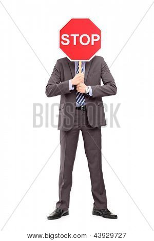 Full length portrait of a man in suit covering his face with a stop sign, isolated on white background