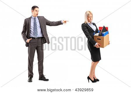 Full length portrait of an angry boss firing a woman with a box of her personal items isolated on white background