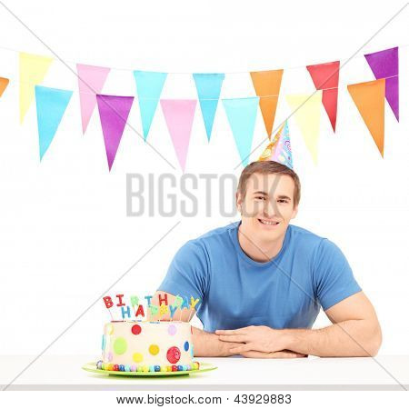 Smiling birthday guy with a party hat and a cake, isolated on white background