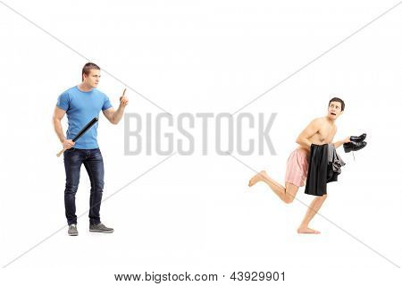 Full length portrait of a violent man holding a baseball bat and embarrassed naked man in underwear isolated on white background